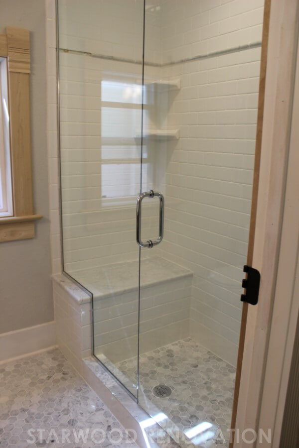 the glass shower doors along with the white tile make the room feel as